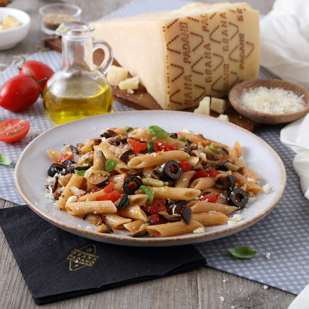 Penne pasta with eggplants, black olive, fresh tomatoes, basil and Grana Padano